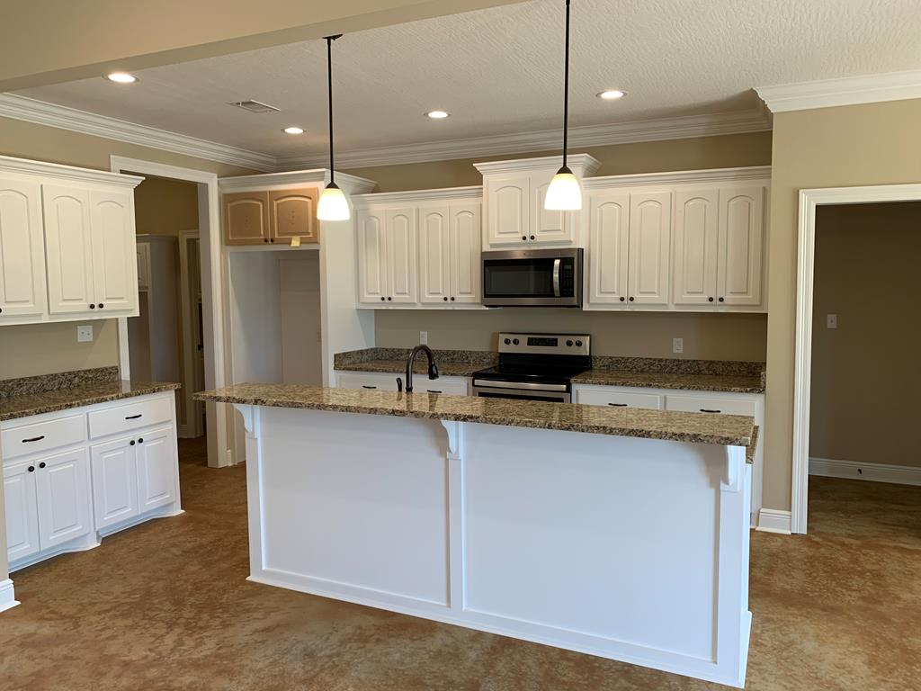 Kitchen with custom cabinetry and granite counter